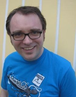 Fabian Mauruschat trägt Brille, meistens keinen Bart und auf diesem Bild ein blaues T-Shirt mit einem Kraken darauf, der ein Schiff umarmt.