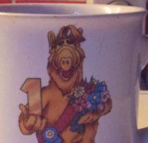 Alf mit einer goldenen Nummer 1 und einem Blumenstrauß in den Händen, aufgedruckt auf einer Tasse.